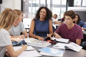 Teacher studying school books in class with high school kids